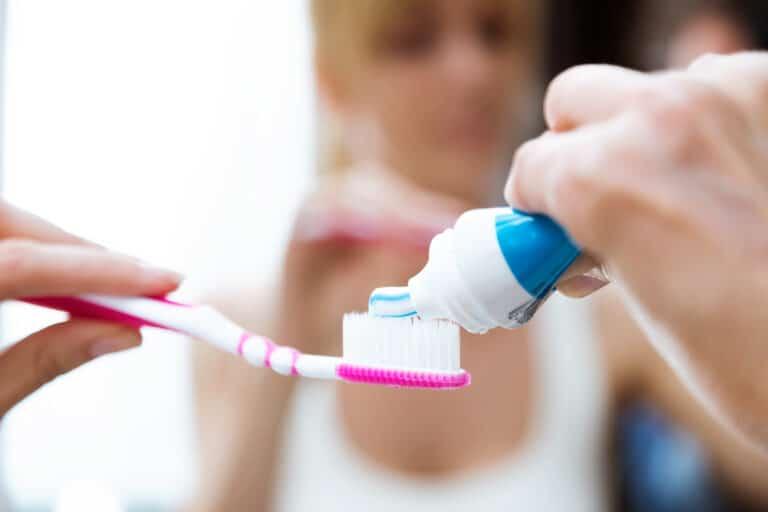 Speilbilde av en som legger tannkrem på en tannbørste.