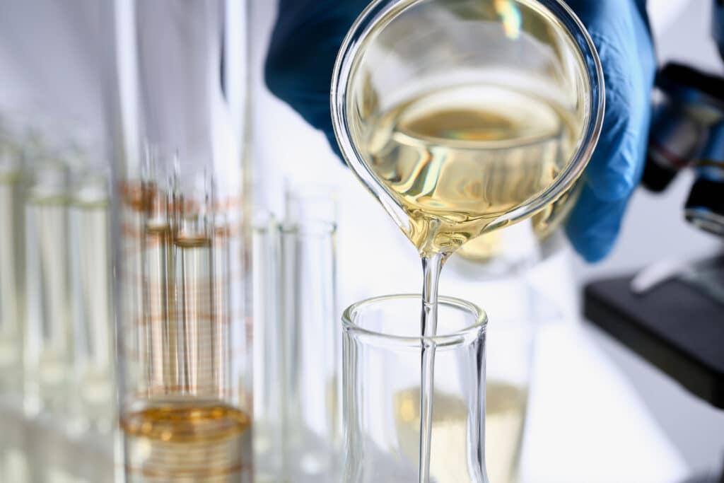 Kjemiker heller et kjemikalium opp i et reagensglass.