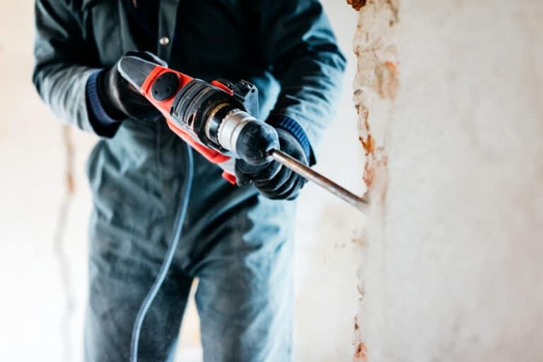 Bygningsarbeider som borrer i betongvegg.