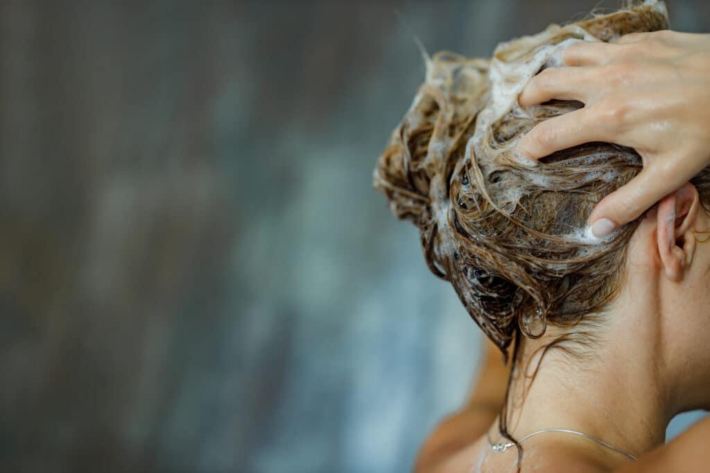 Kvinne som vasker håret med sjampo.