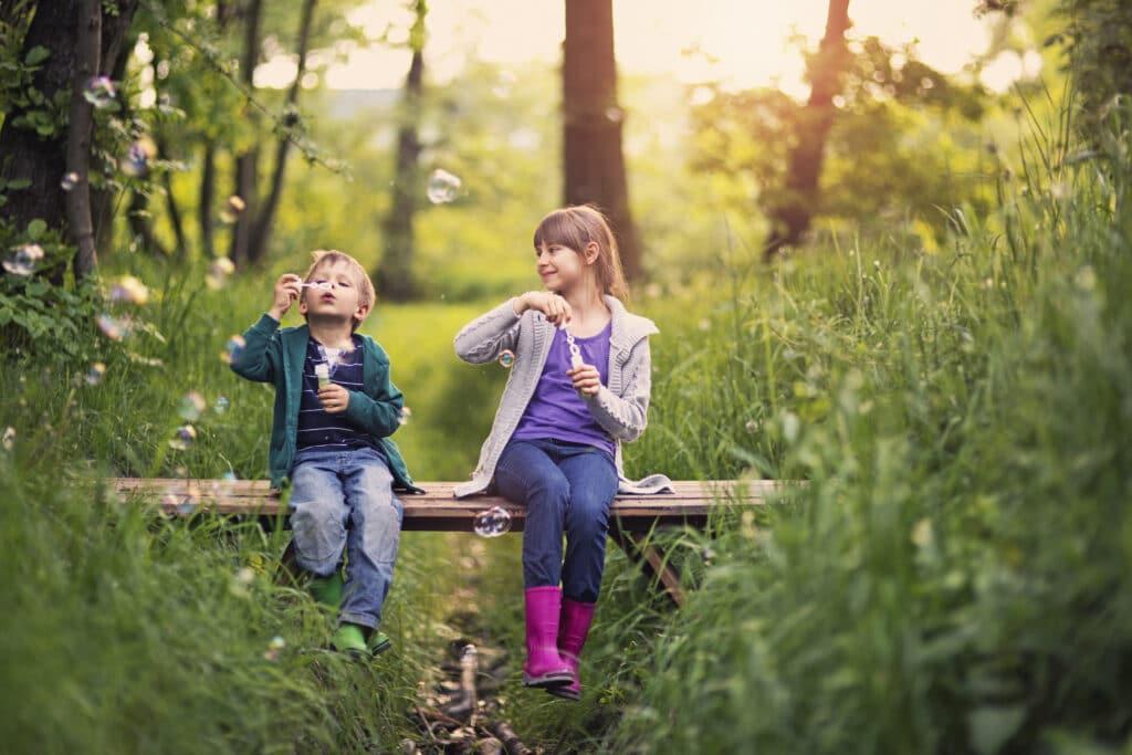 To barn som blåser såpebobler i det grønne.
