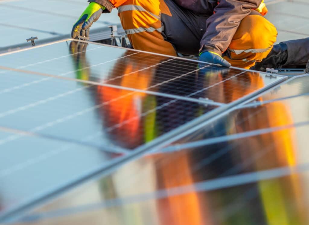 En mann som legger solcellepanel.