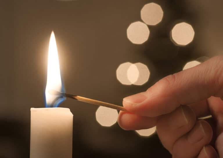 Nærbilde av hånd som tenner et lys.