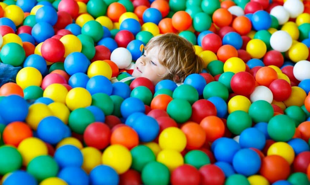 Barn som ligger blant mange fargerike baller.