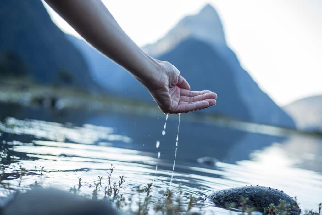 Kvinnehånd kjenner på vannet i en innsjø til fjells.