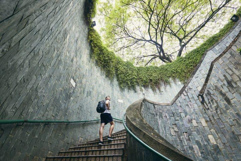 Mann går opp spiraltrapp med utsikt til tretopper